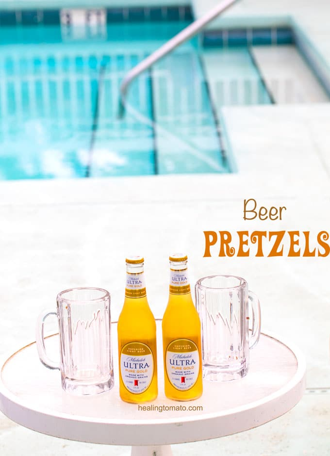Two bottles of Michelob ULTRA Pure Gold on a glass table with beer glasses next to it and a swimming pool in the back - Beer Pretzel Bites