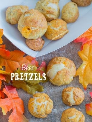 Overhead view of beer pretzel bites on a brown surface surrounded by fall leaves