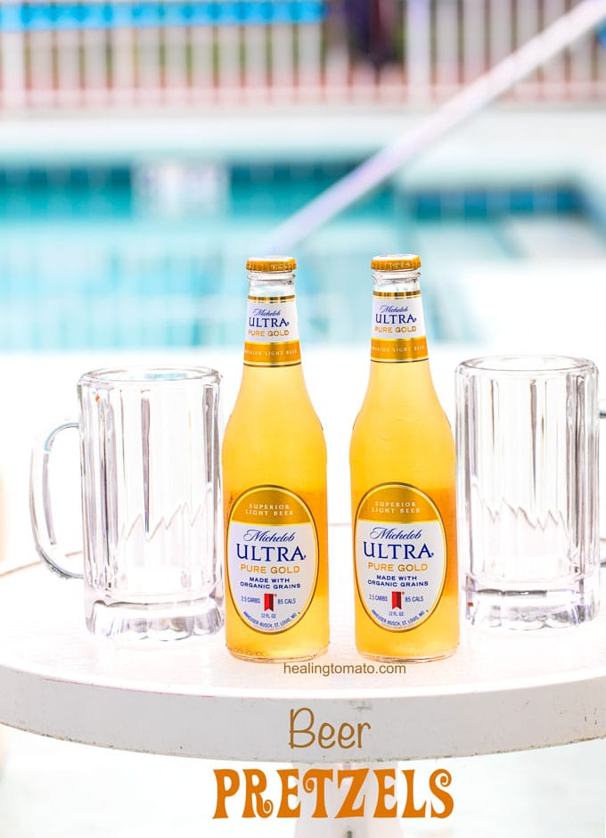 Closeup view of Two bottles of Michelob ULTRA Pure Gold on a glass table with beer glasses next to it and a swimming pool in the back - Beer Pretzel Bites