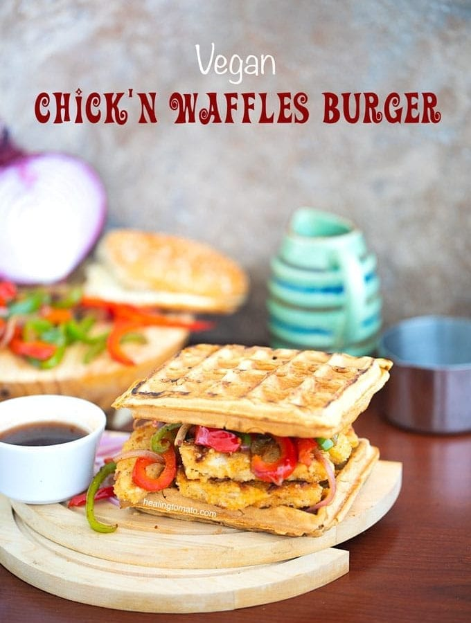 Angle view of a waffle burger with sauce on the side and grilled veggies in the back - Chickn and Waffle Burgers