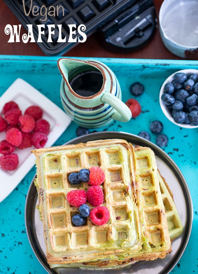 Overhead view of vegan kale waffles topped with raspberries and blueberries on a blue tray. Its surrounded by blueberries, raspberries and a small mug filled with maple syrup.