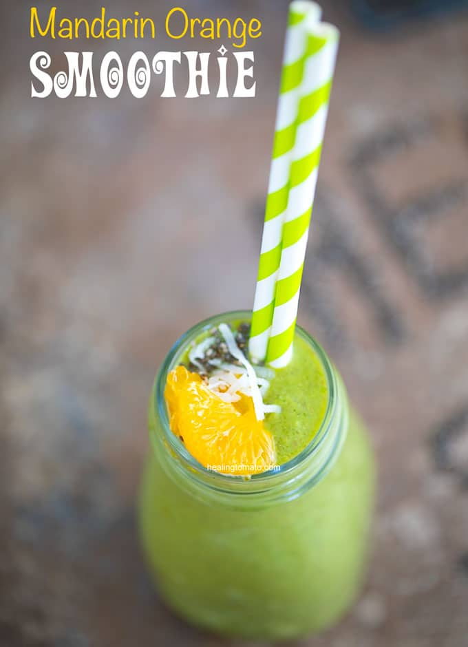 Overhead view of the green smoothie with mandarin oranges, coconut shreds and chia seeds for garnish. 2 green paper straws on coming out of the bottle