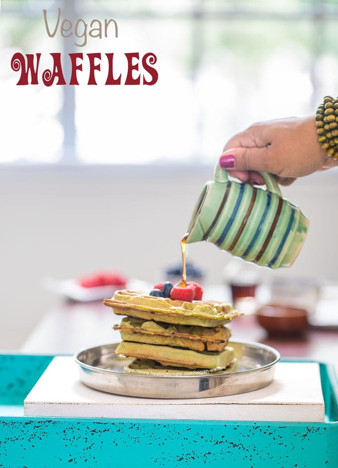 Front view of a stack of 4 kale vegan waffles topped with blueberries and raspberries. A drizzle of maple syrup is being dropped from the top by the author
