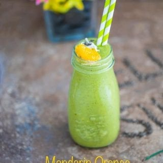 Front view of a glass milk bottle filled with the green smoothie and has 2 plastic straws. Garnished with mandarin oranges and chia seeds. A glass flower vase in the background