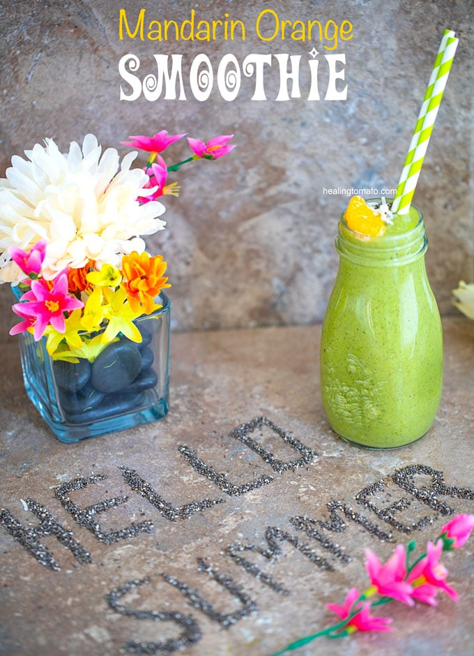 "Overhead veiw of a brown tile with ""Hello Summer"" written out in chia seeds and a glass bottle with green smoothie on the side and a glass flower vase on the top left"