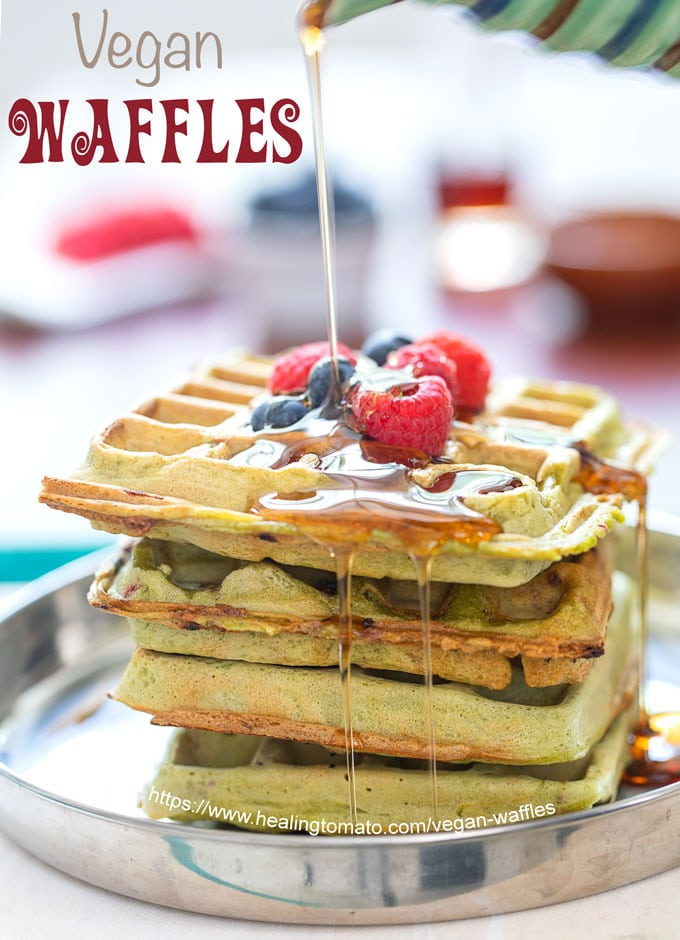 Front view of a stack of 4 kale vegan waffles topped with blueberries and raspberries. A drizzle of maple syrup is being dropped from the top