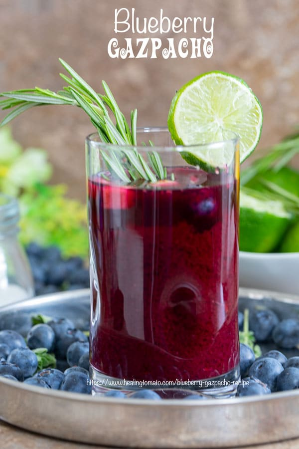 Front view of a glass filled with Gazpacho soup and garnished with Lime and Rosmary Stem. Glass surrounded by blueberries, lime and flowers