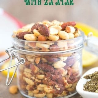 Front view of Mixed Nuts with Za'atar spice in a mason jar. Surrounded by za'atar spice and lemon rounds
