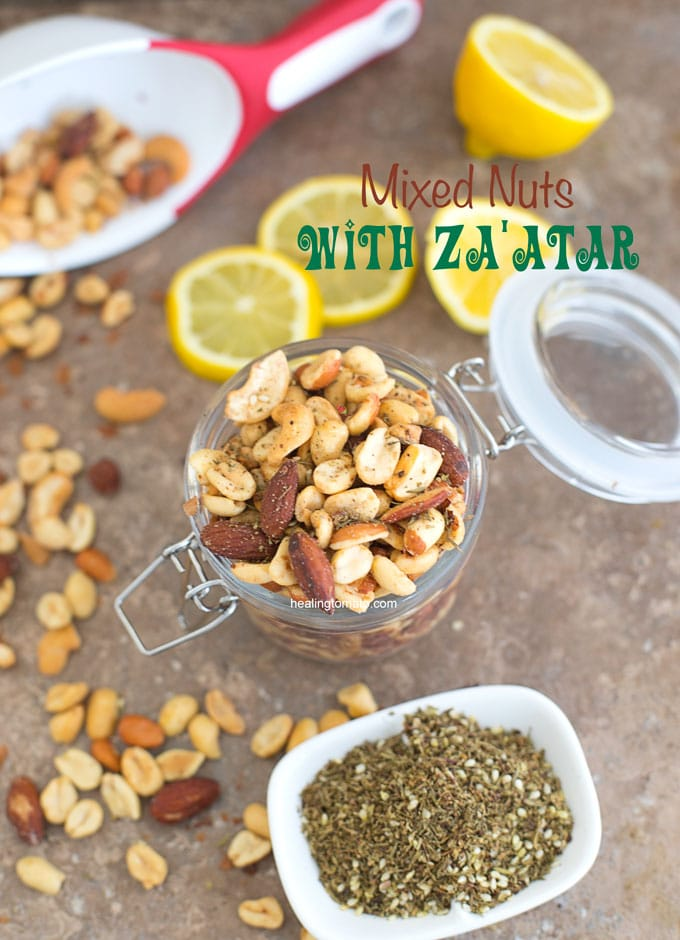 Overhead view of Mixed Nuts with Za'atar spice in a mason jar. Surrounded by za'atar spice and lemon rounds