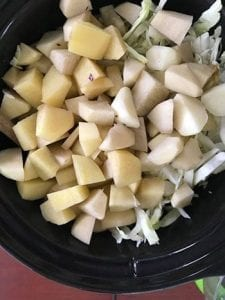 cubed potatoes added to the slow cooker - Cabbage Curry