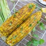 Overhead view of 2 Corn on the cob cooked and spread with a cilantro sauce
