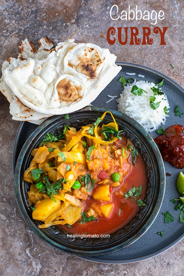 Overhead view of a metallic grey bowl filled with cabbage curry in a red sauce. Bowl surrounded by naan, rice, pickels and lime - Vegan Cabbage Curry