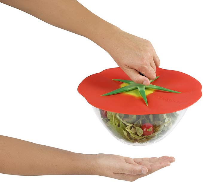 a hand is holding the tomato silicon lid on a salad bowl