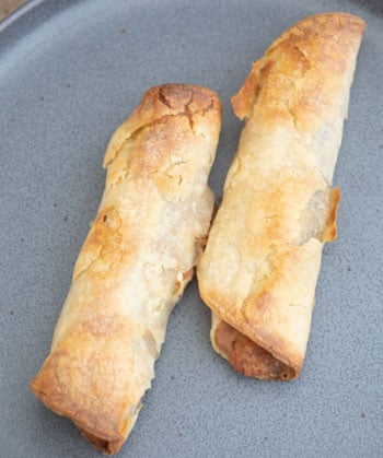 Overhead view of two baked vegan taquitos on a grey plate
