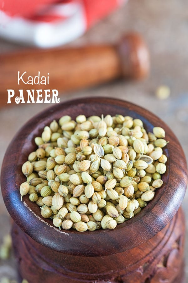 Coriander seeds in a brown wooden morter and pestel in the back - kadai paneer