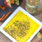 Overhead view of a white plate with Greek seasoning mix surrounded by Autumn leaves and a jar of Greek Seasoning mix