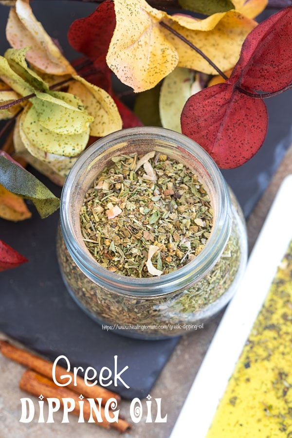 Overhead view of a glass jar filled with Greek Seasoning Mix and surrounded by Autumn leaves and Greek dipping oil