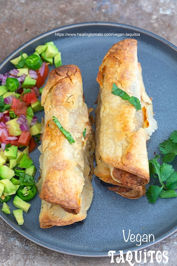 Overhead view of baked vegan taquitos on a grey plate with avocado salsa next to it