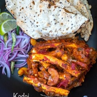 Overhead view of kadai paneer with papad and onions