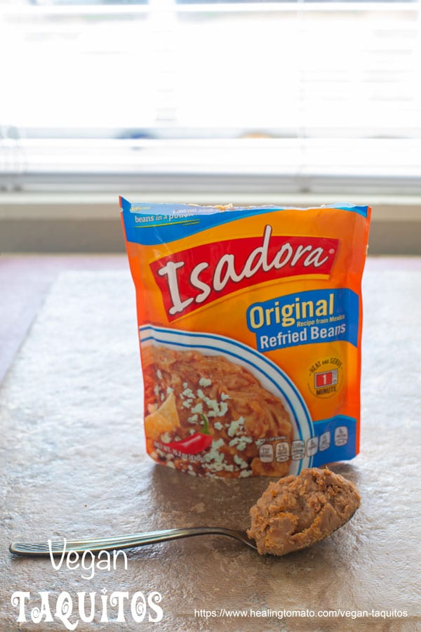 front view of a packet of isadora refried beans with a spoon next to it - Vegan Taquitos