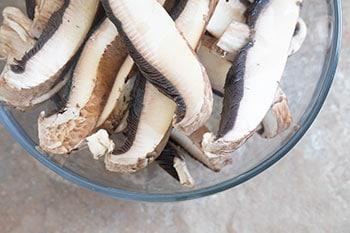 Oiled Portobello Mushrooms sliced in a bowl - Vegan Taquitos