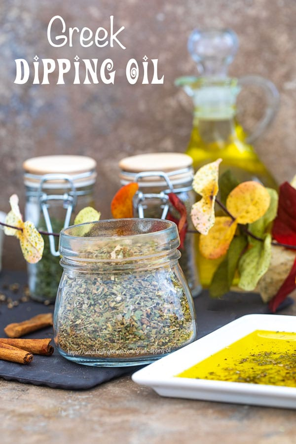 Front view of a glass jar filled with Greek Seasoning Mix and surrounded by Autumn leaves and Greek dipping oil