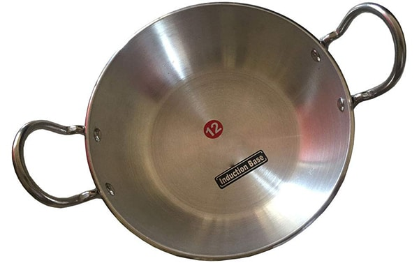 Overhead view of a aluminium kadai on a white surface - kadai paneer