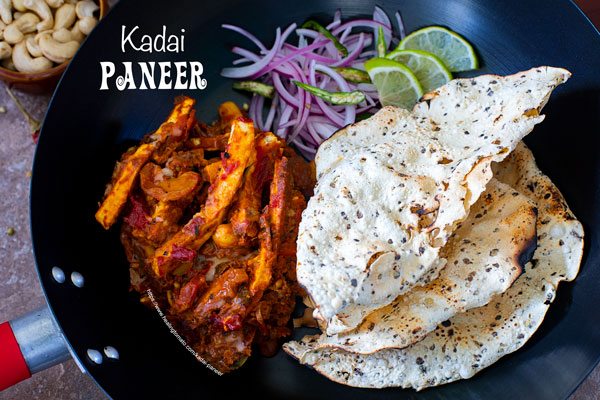 Landscape view of the black kadai filled with kadai paneer, onions and papad
