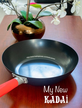 The author's new wok with a red handle on a brown table - kadai paneer