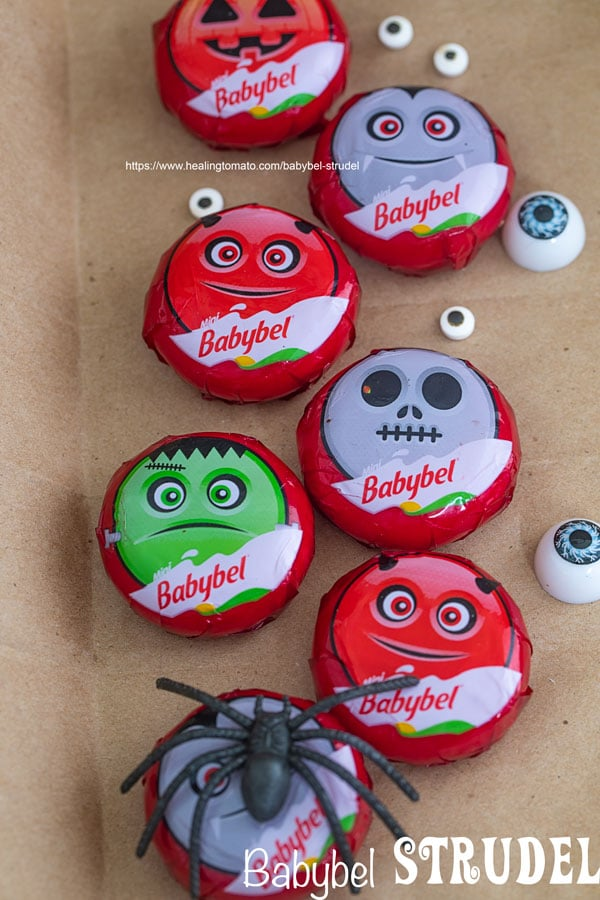 Mini Babybel Cheeses arranged in two rows, surrounded by candy eyes and fake spiders - Babybel Strudel