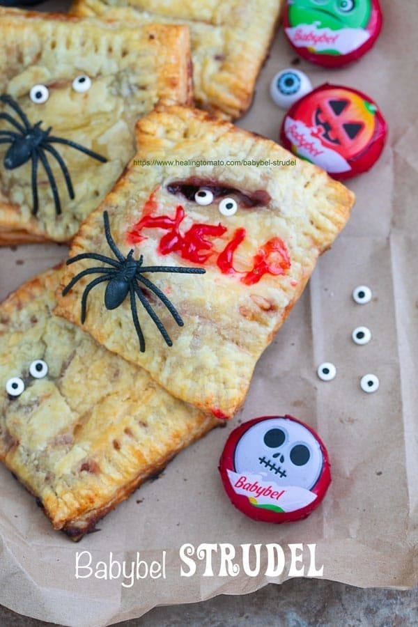 "Closeup view of a Babybel strudel surrounded by Babybel cheese, candy eyes and spiders. One of the strudels has the word ""HELP"" written with icing - Babybel Strudel"