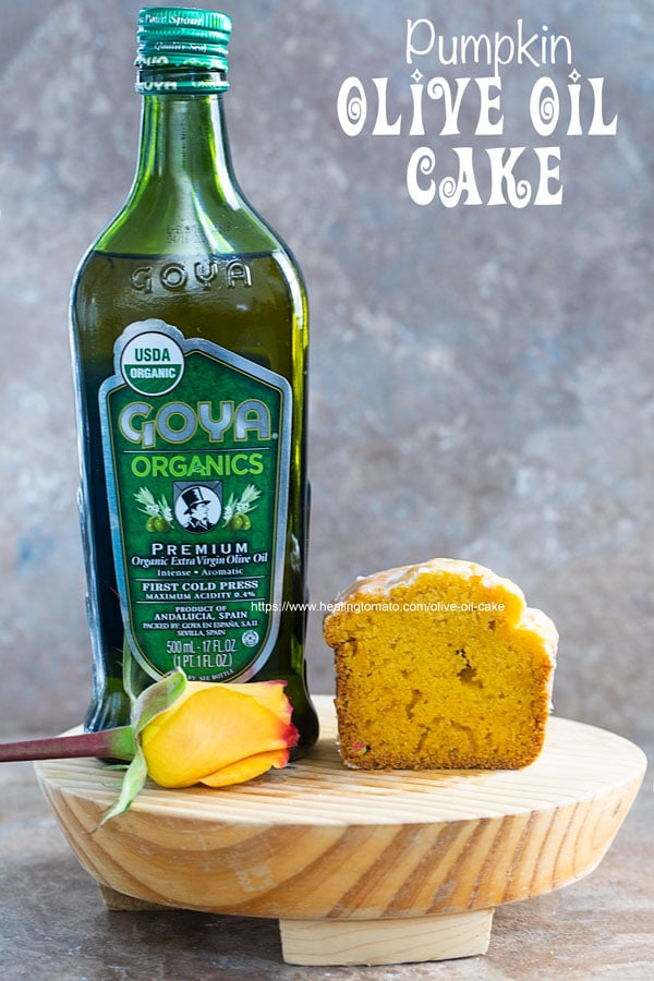 Front view of Goya Organics Premium Extra Virgin Olive OIl with a crossection of olive oil cake and a rose all on a brown board
