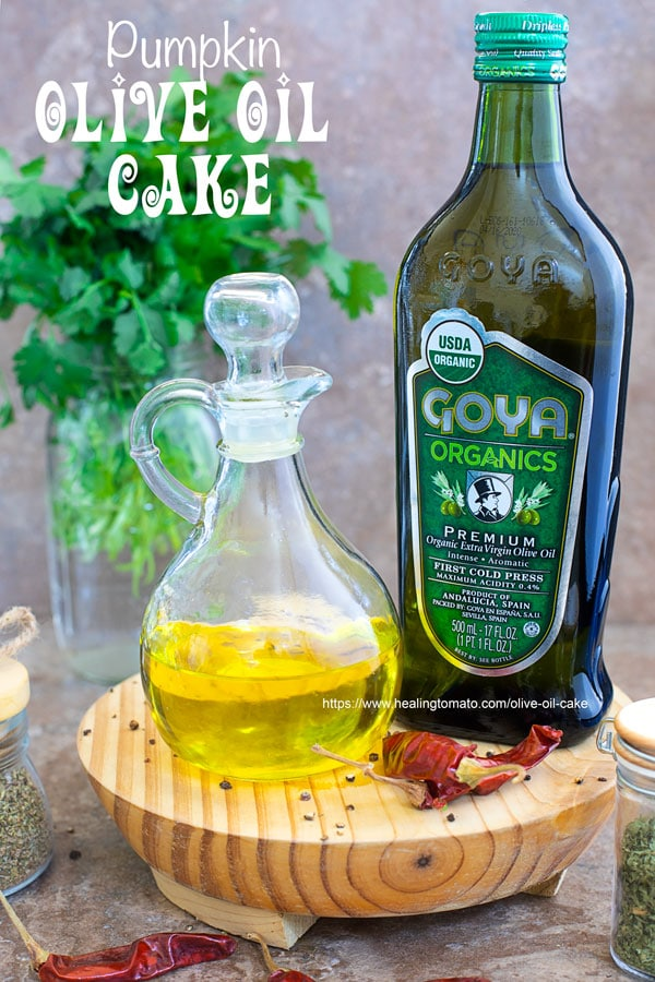 Front view of Goya Organics Premium Extra Virgin Olive OIl surrounded by garnish and a vase of cilantro