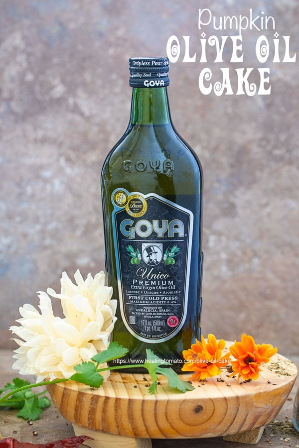 Front view of Goya Unico Premium Extra Virgin Olive OIl on a brown board surrounded by flowers