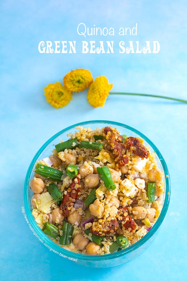 Closeup view of a bowl on a blue background. Bowl is filled with quinoa, green beans and chick peas. Garnished with cilantro and orange slices. Small yellow carnations on the side - Green Bean Salad