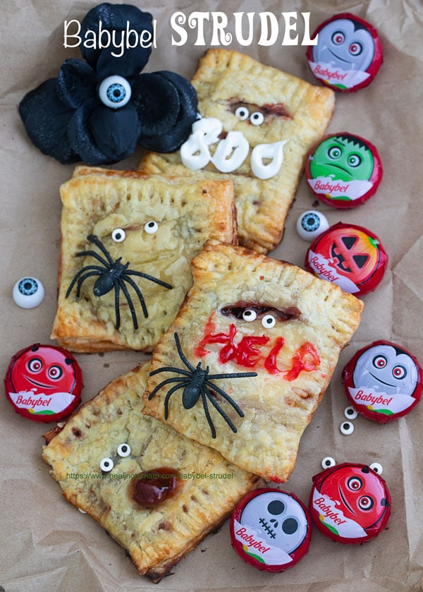 "Overhead view of Strudels surrounded by Babybel cheese, candy eyes and spiders. One of the strudels has the word ""HELP"" written with red icing and one has ""BOO"" written in white icing"