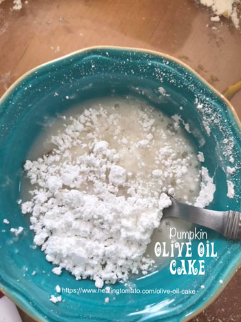 A blue bowl filled with powdered sugar and almond milk with a spoon stirring it - Vegan Pumpkin Olive Oil Cake