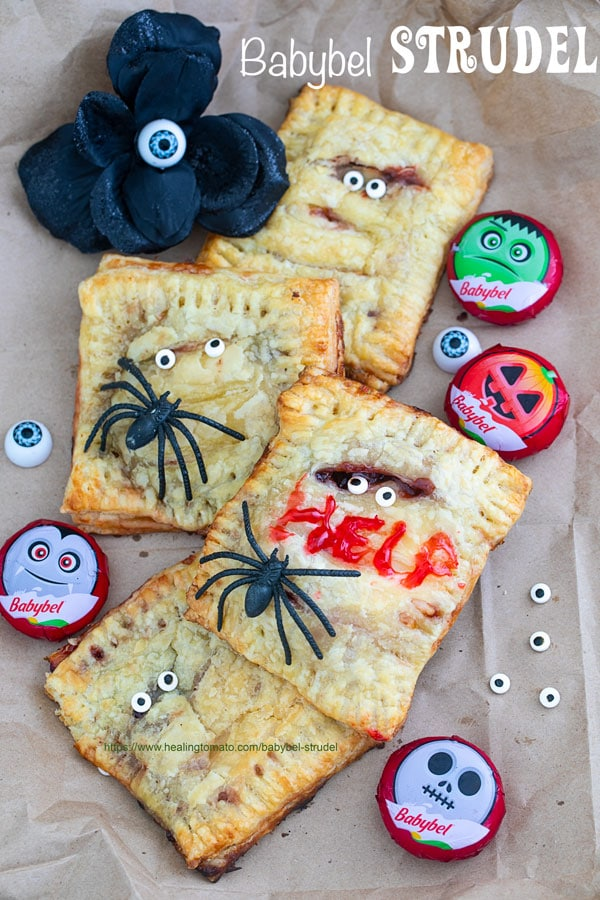 """Overhead view of Babybel strudels surrounded by Babybel cheese, candy eyes, faux black flower and fake spiders. One of the strudels has the word """"HELP"""" written with icing - Babybel Strudel"""