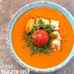 Overhead view of a blue bowl with cream tomato soup