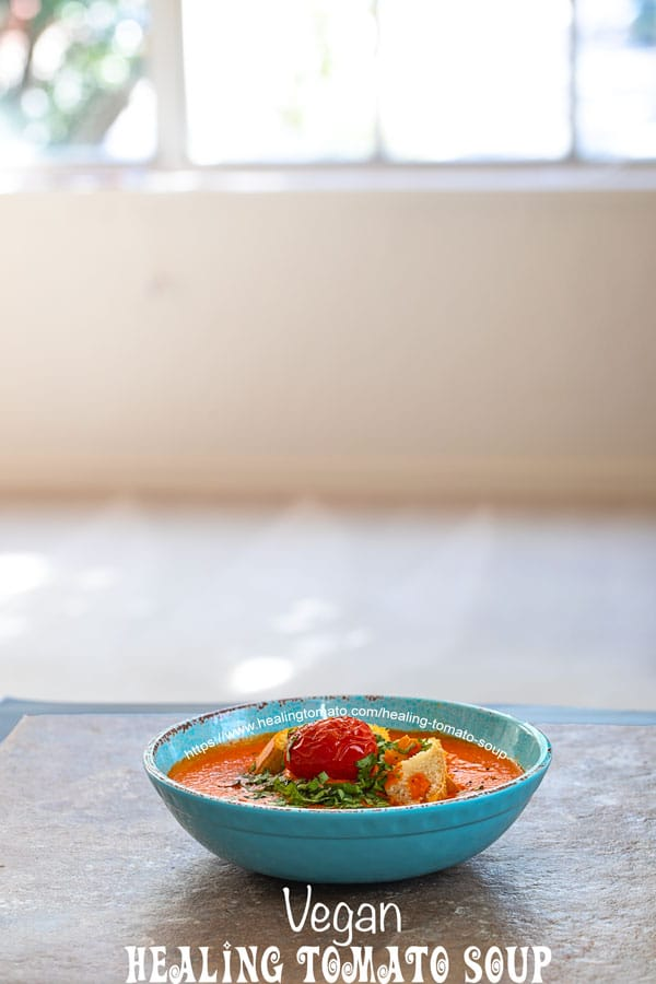 front view of tomato soup in a blue bowl with a big window behind