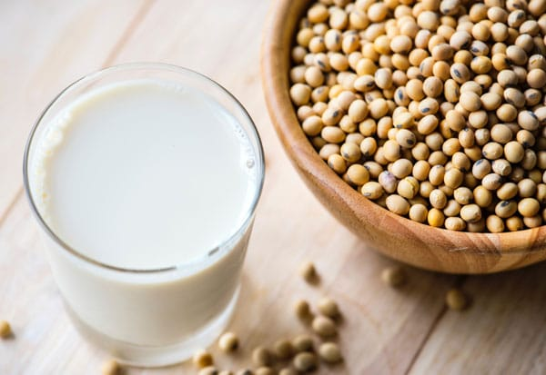 A glass of milk next to a bowl of soy beans - What Vegans Don't Eat
