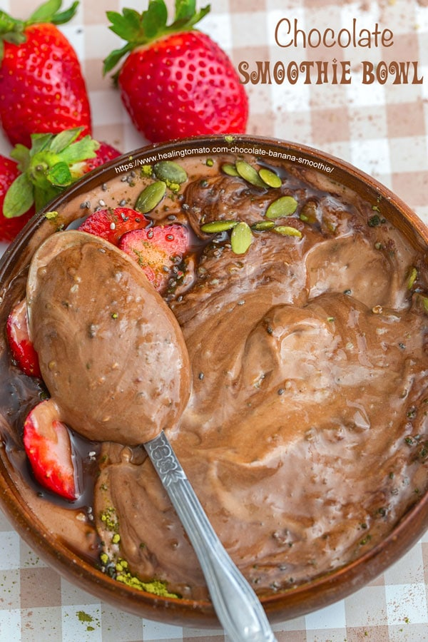 Top view of a spoon filled with chocolate banana smoothie in a bowl -