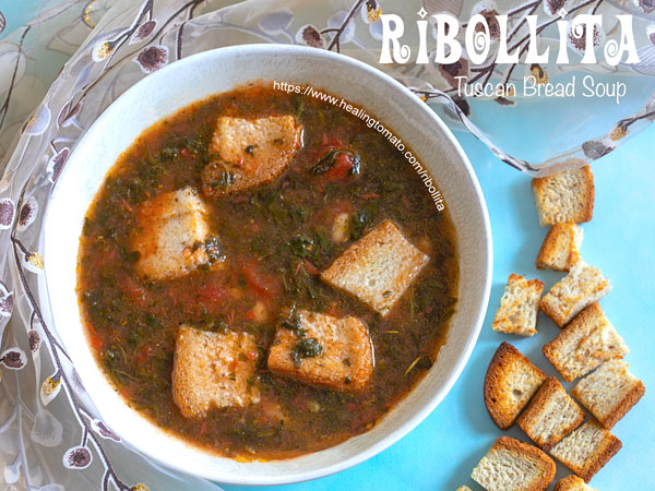 Overhead closeup of ribollita soup in a bowl and small bread cubes on the side