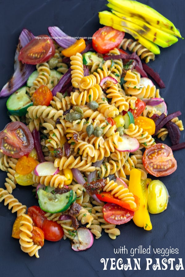 Overhead view of vegan pasta with grilled veggies on a black plate.