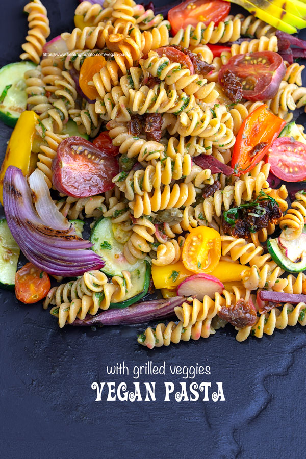 Overhead view of vegan pasta with grilled veggies on a black plate