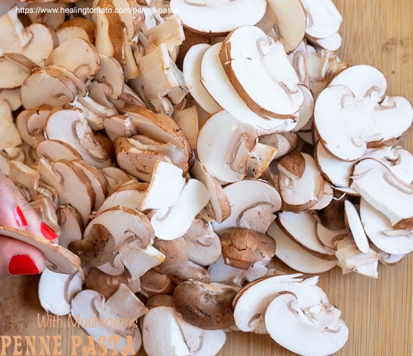 Overhead view of thinly sliced mushrooms on a brown chopping board - penne pasta