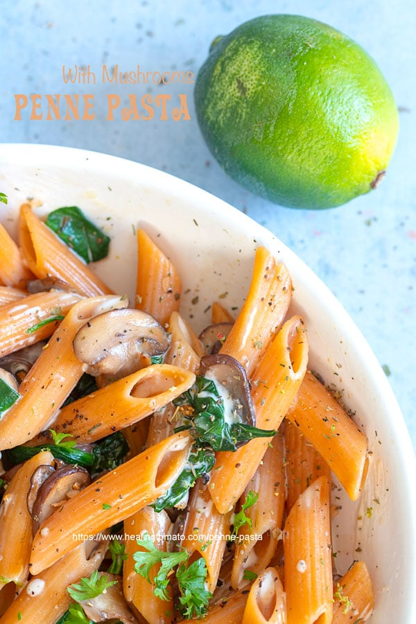 Closeup view of penne pasta in a bowl next to a zested lime