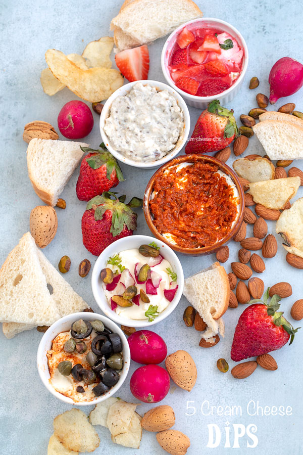 Top view of all 5 cream cheese dips surrounded by fruits, veggies and nuts