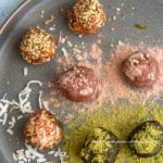 Close-up view of 7 no bake energy bites on a dark grey plate