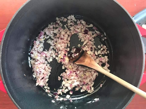 onions added to the pan and a wooden stick mixing them